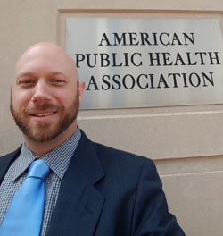 Smiling Ben King in front of American Public Health Association sign