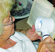 Woman using magnifying reading device