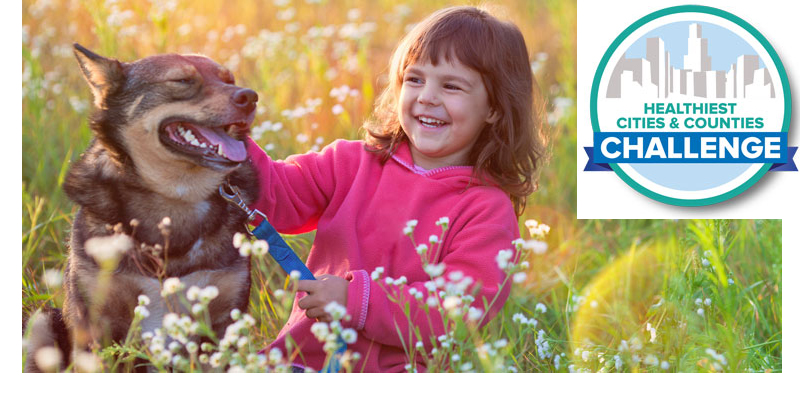 smiling girl and smiling dog in field of tall grass and flowers, Healthiest Cities & Counties Challenge logo