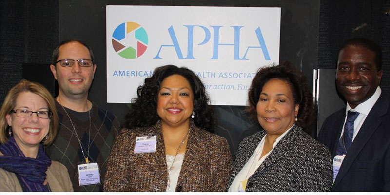 two men and three women smiling in front of APHA logo