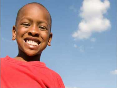 boy smiling with blue sky and one cloud in background